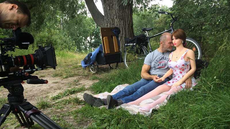 Mann mit lebensgoßer Puppe auf einer Wiese sitzend