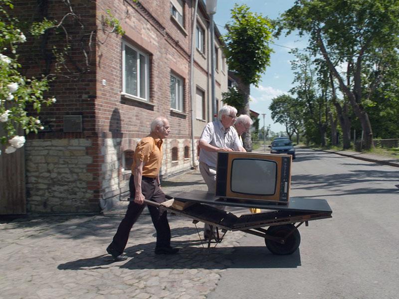 Ein Fernseher wird auf einer Schubkarre transportiert